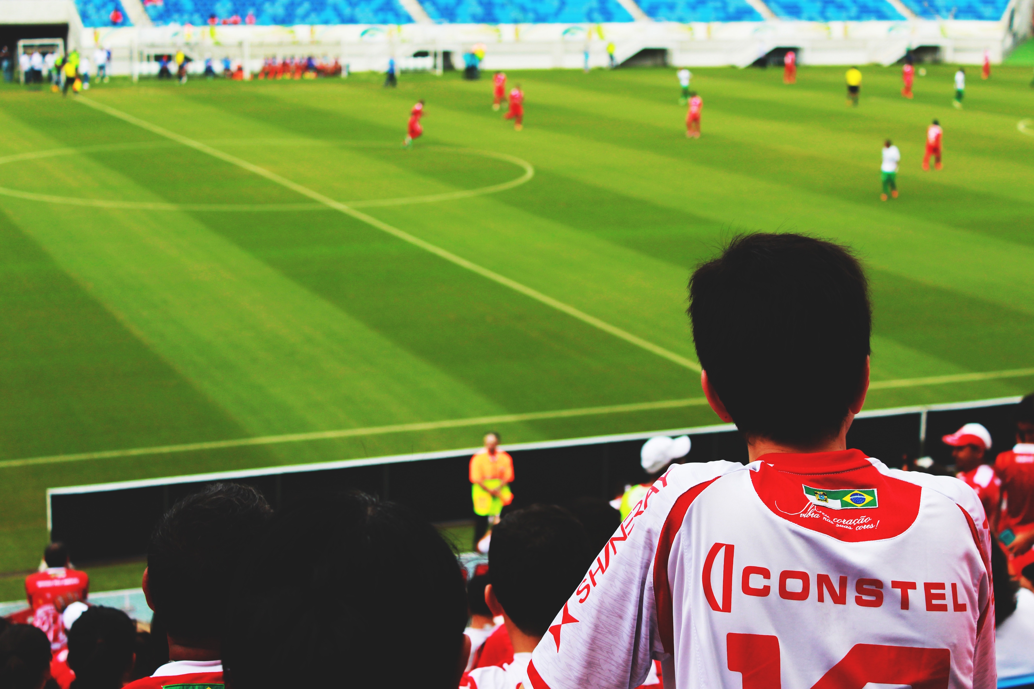 A young pectator is looking football players from the stands of a stadium. The Cross Language Processing help the crowd to understand what happen through display