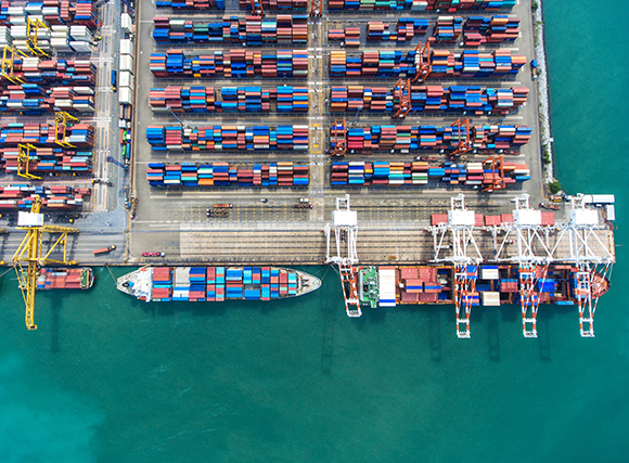 A harbor seen from the sky. Boat and docks with containers This show the internalization of trade and justify the Impact of Automated Translations on Multilingual Trade Systems