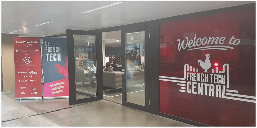 OpenNMT-tf 2.0 workshop. Red Kakemonos and French Tech Central logo in front of the entrance door of Station F held in Paris in March 2018.